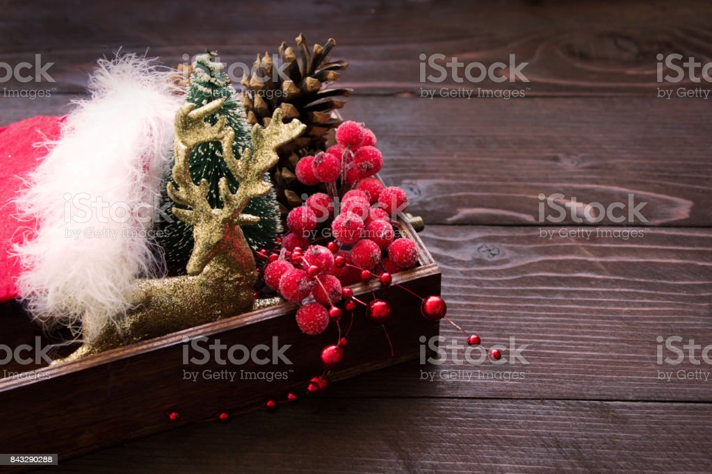 Christmas composition with golden deer. red berries, cones in wooden box, place for text stock photo