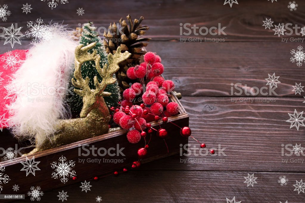 Christmas composition with golden deer. red berries,white snowflakes , cones in wooden box, place for text stock photo