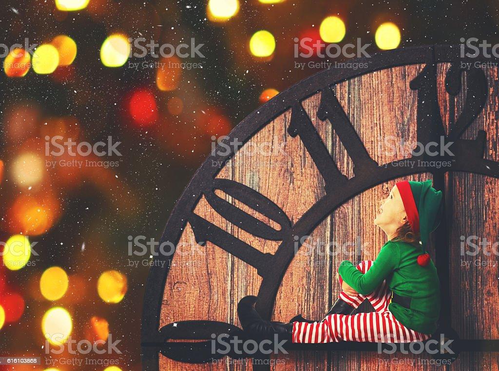 Christmas concept. Little Elf on clockwise stock photo
