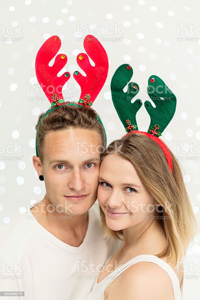 Christmas couple pose for portrait in reindeer headbands: cute! stock photo