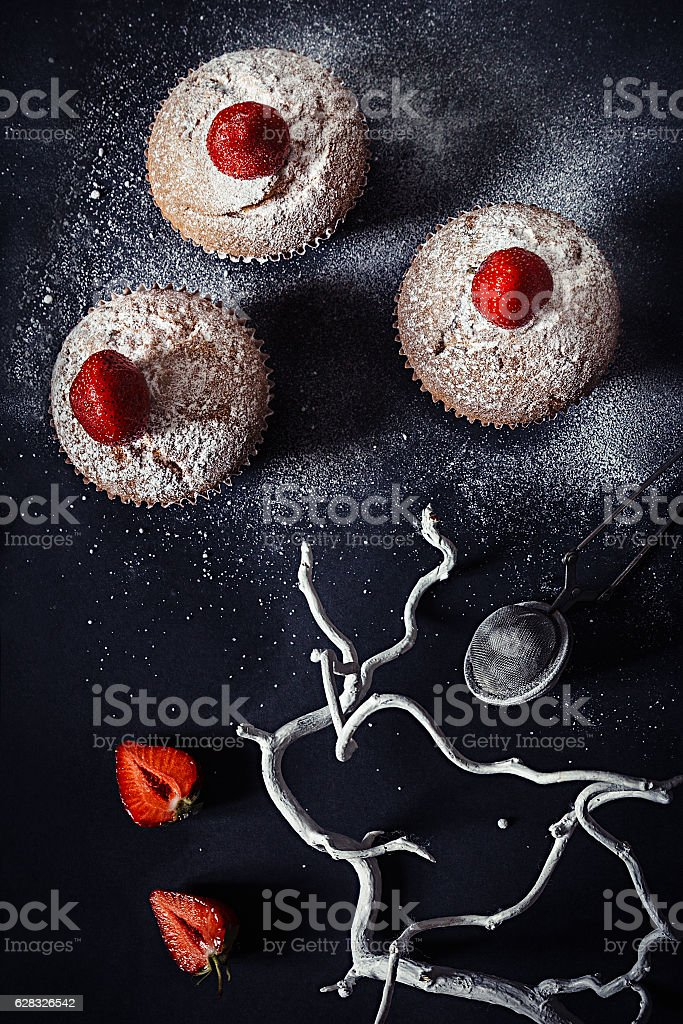 Christmas cupcakes with strawberries and powdered sugar   black background. stock photo