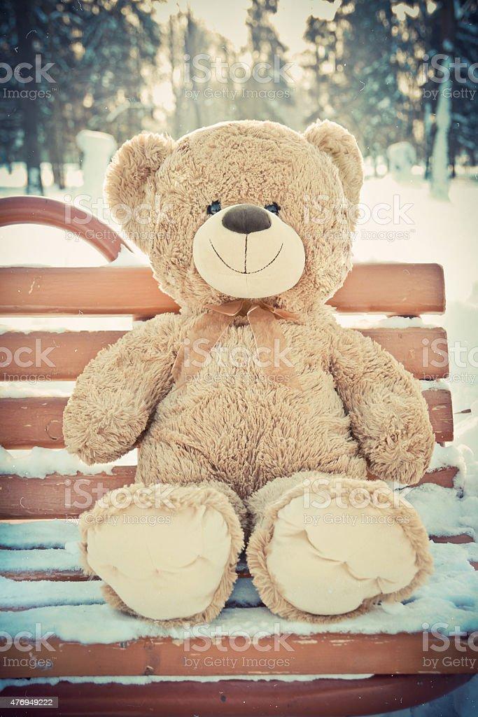 Christmas. Cute Teddy  bear on the bench silit with snow. stock photo