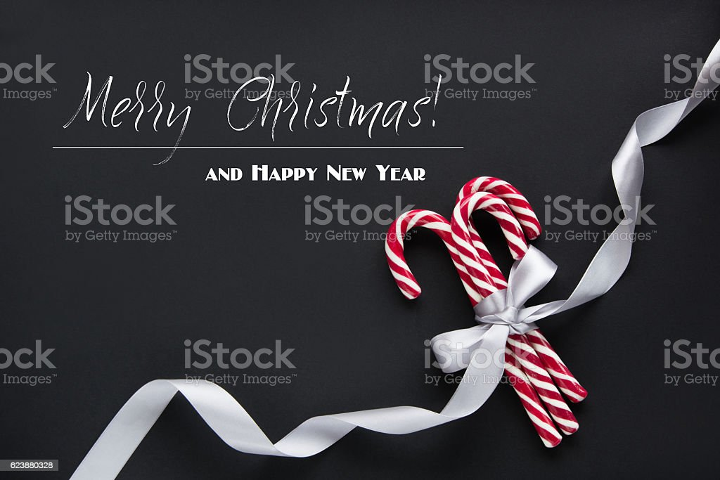 Christmas decoration composition from candy cane on black with congratulation. stock photo