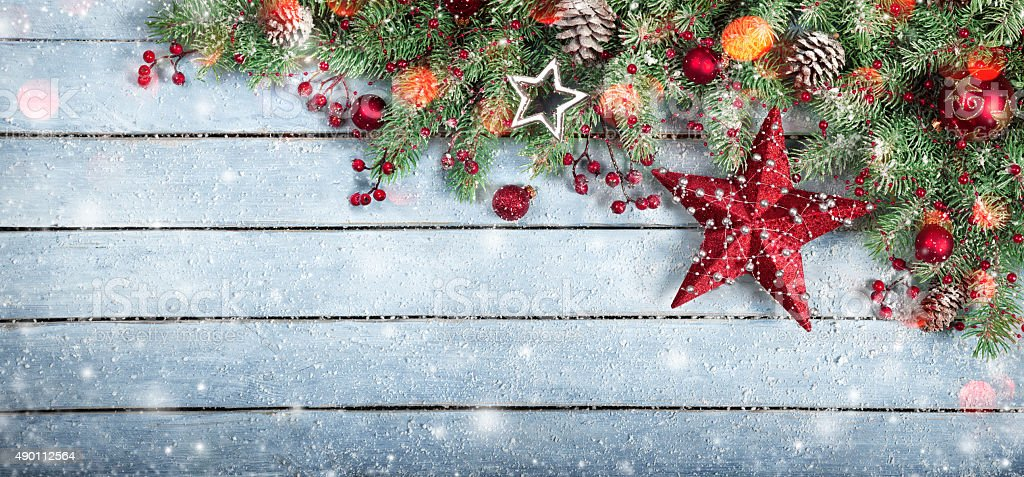Christmas decoration with holly baubles on snowy plank stock photo