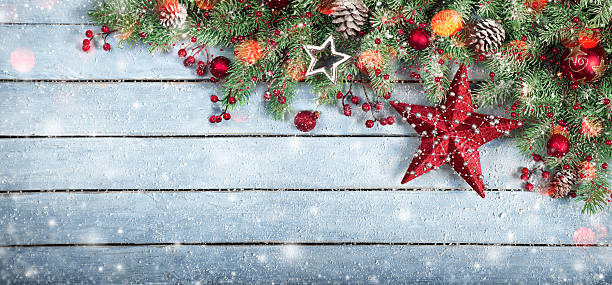 christmas decoration with holly baubles on snowy plank stock photo - Christmas Decoration