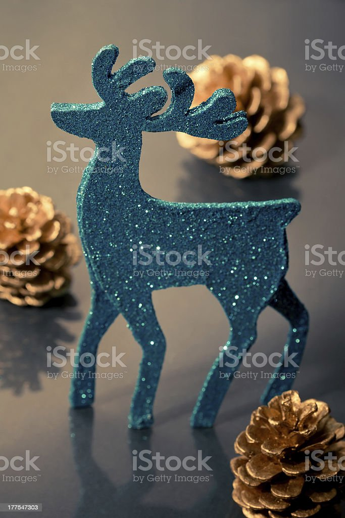 Christmas decorations: reindeer figure and golden cones, closeup royalty-free stock photo