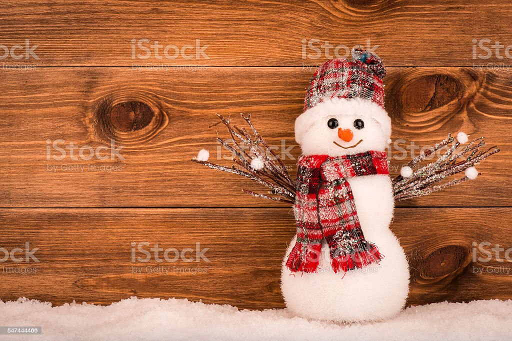 Christmas decorative snowman on brown wooden background. stock photo