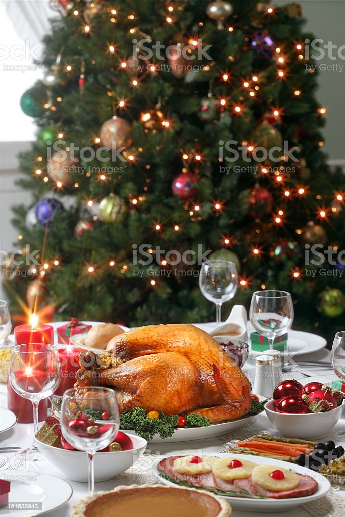 Christmas dinner with a Christmas tree in the background royalty-free stock photo
