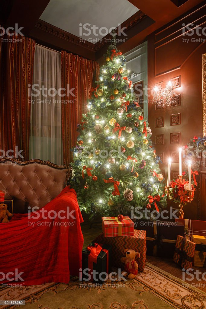 Christmas evening by candlelight. classic apartments with a white fireplace stock photo