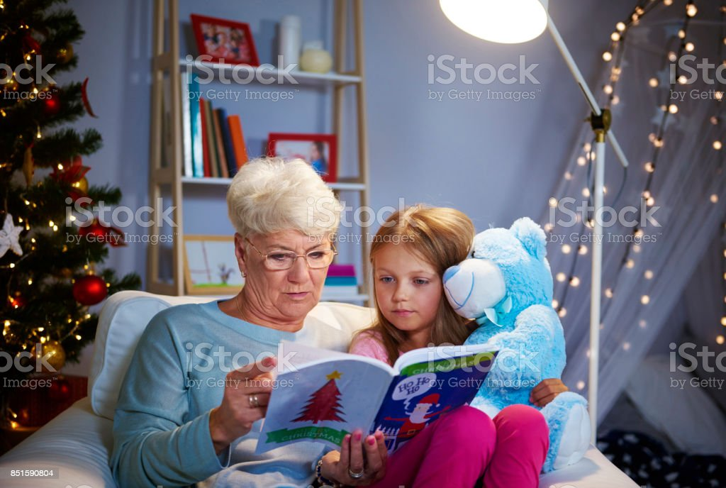Christmas evening with grandmother, storybook and teddy bear stock photo