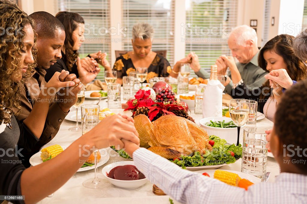 Multi-ethnic family and friends pray during Chiistmas dinner....