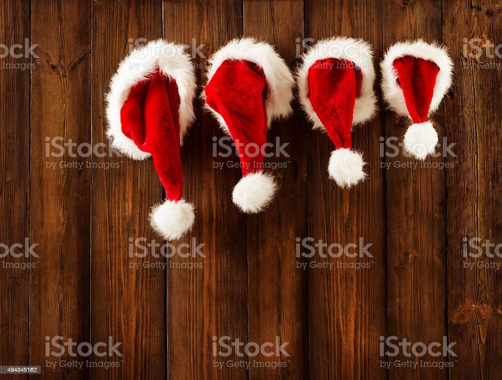 Christmas Family Santa Claus Hats Hanging, Wood Wall, Xmas Hat stock photo