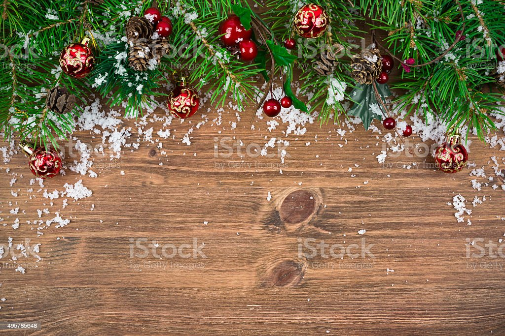 Christmas fir tree with snow on wooden background stock photo