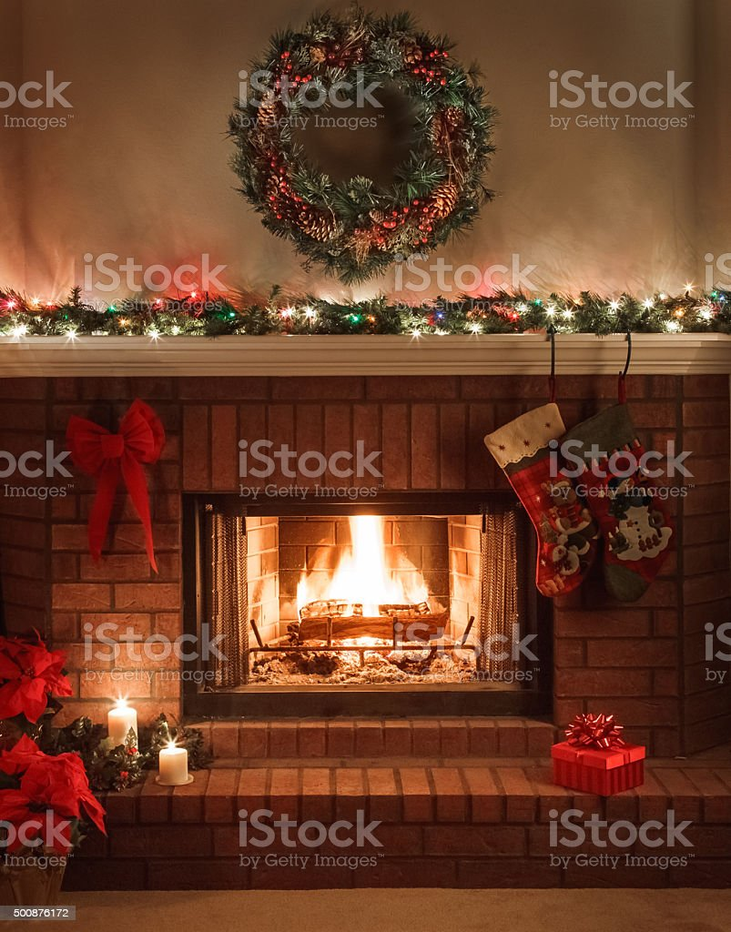 Christmas Fireplace, holiday decorations, cozy fire, wreath, lights on mantel stock photo