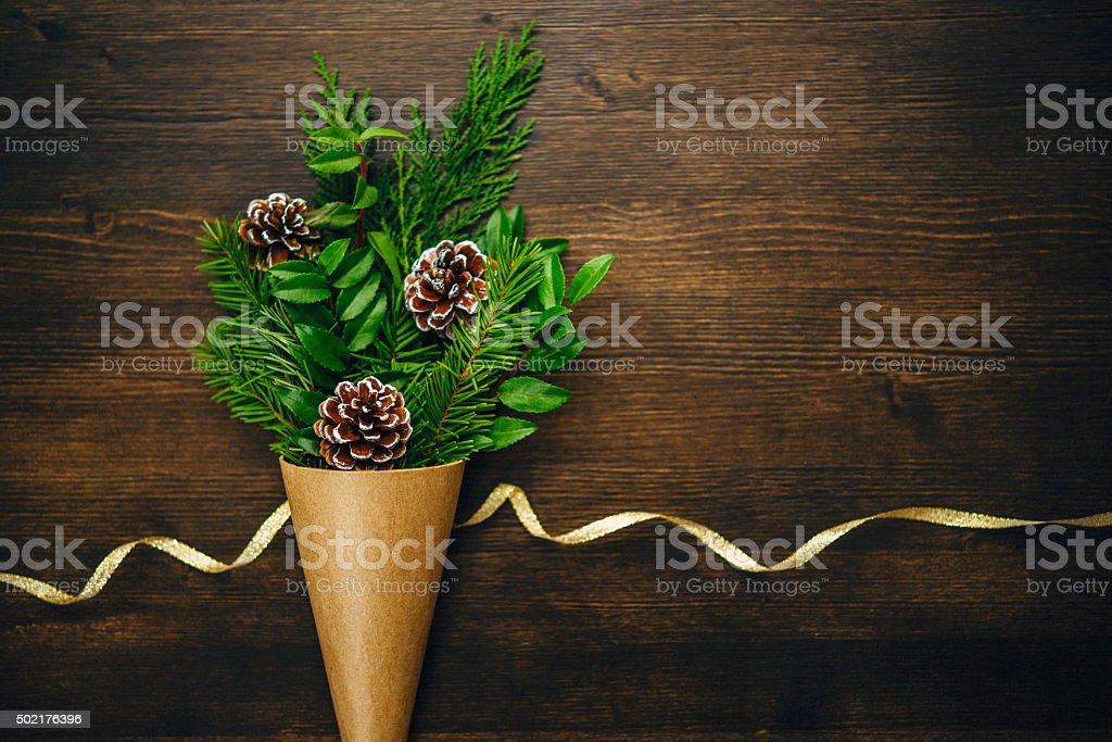 Christmas foliage arrangement with pinecones on rustic wood table stock photo