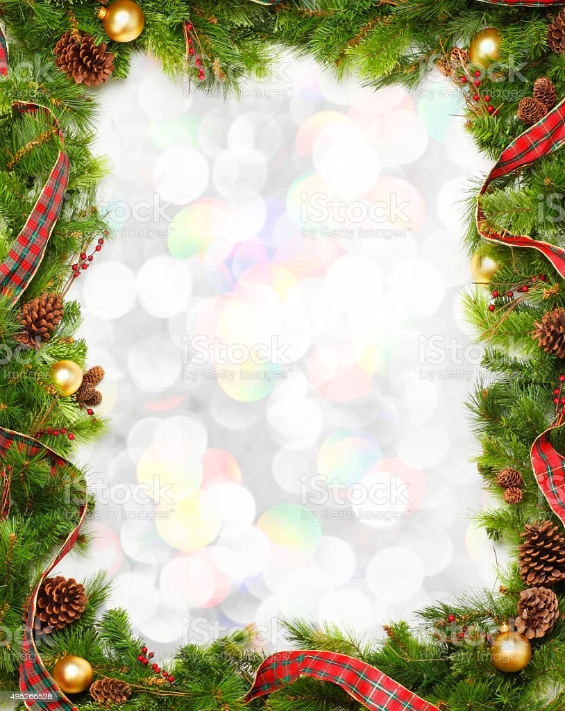 Christmas Garland Frame In Front Of Blurred Lights stock photo