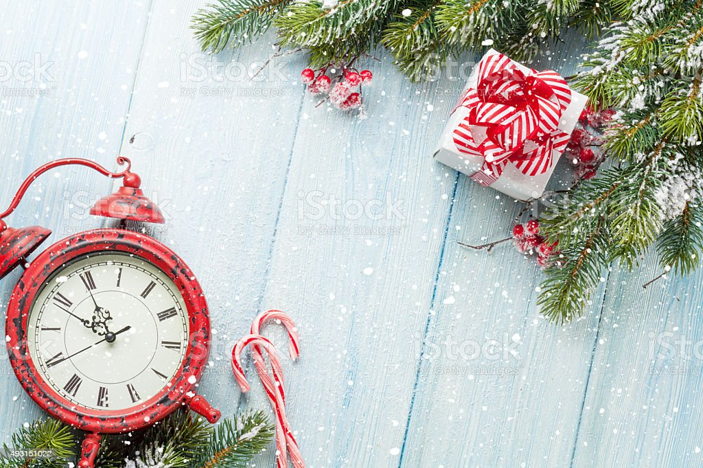 Christmas gift box, alarm clock, candy cane and fir tree stock photo