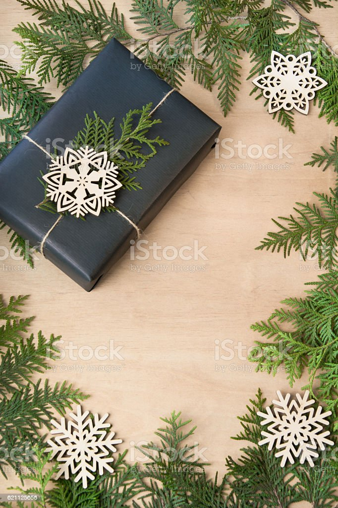 Christmas gift box in black paper on wooden surface. Copy-space. stock photo