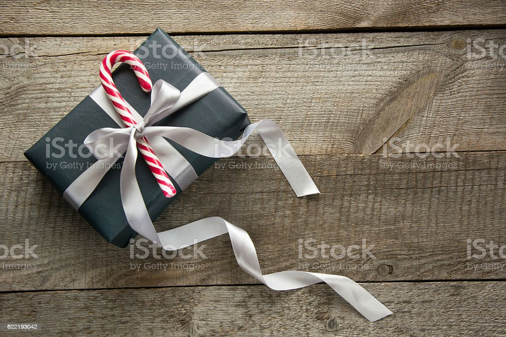 Christmas gift box in black paper with candy on board. stock photo