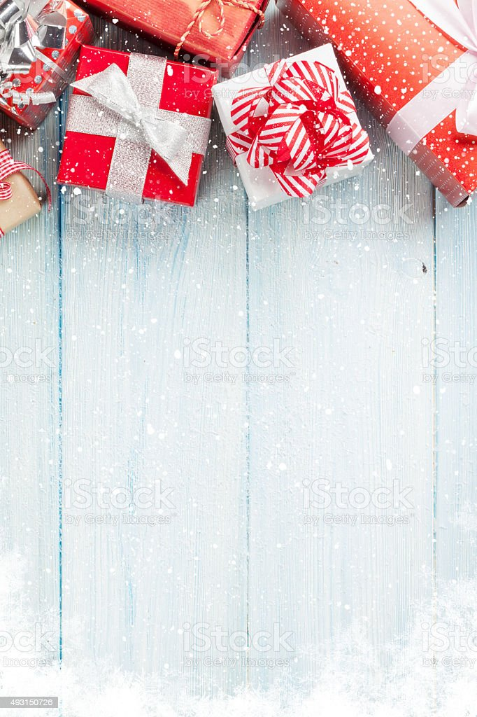 Christmas gift boxes on wooden table with snow. Top view with copy...