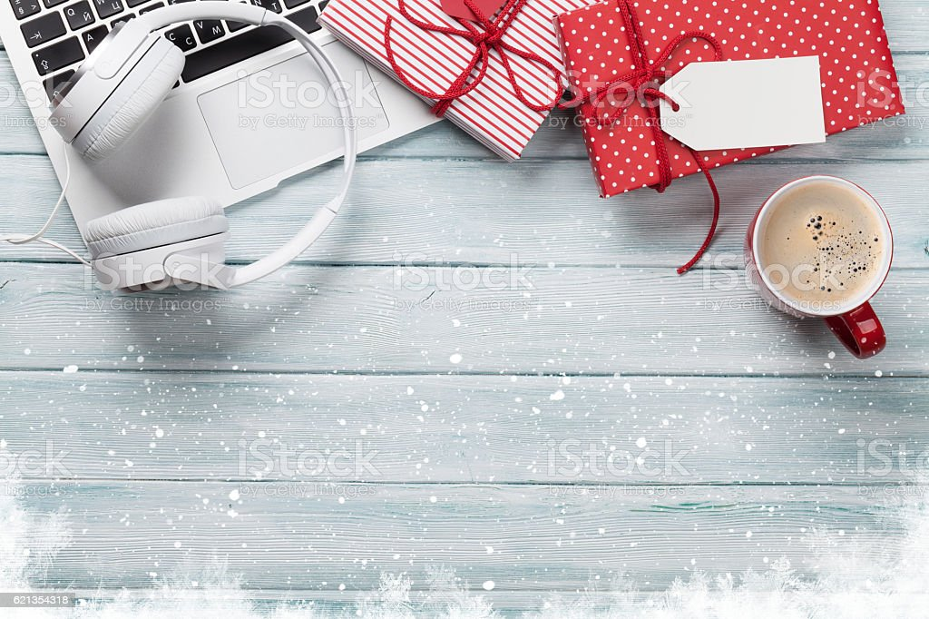 Christmas gift boxes, pc and coffee cup on wood stock photo