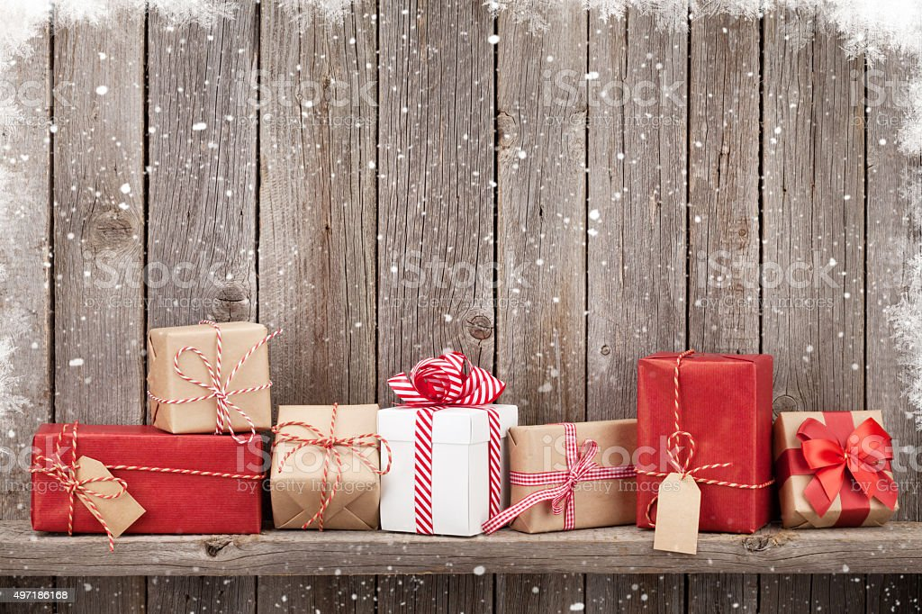 Christmas gift boxes in front of wooden wall with copy space