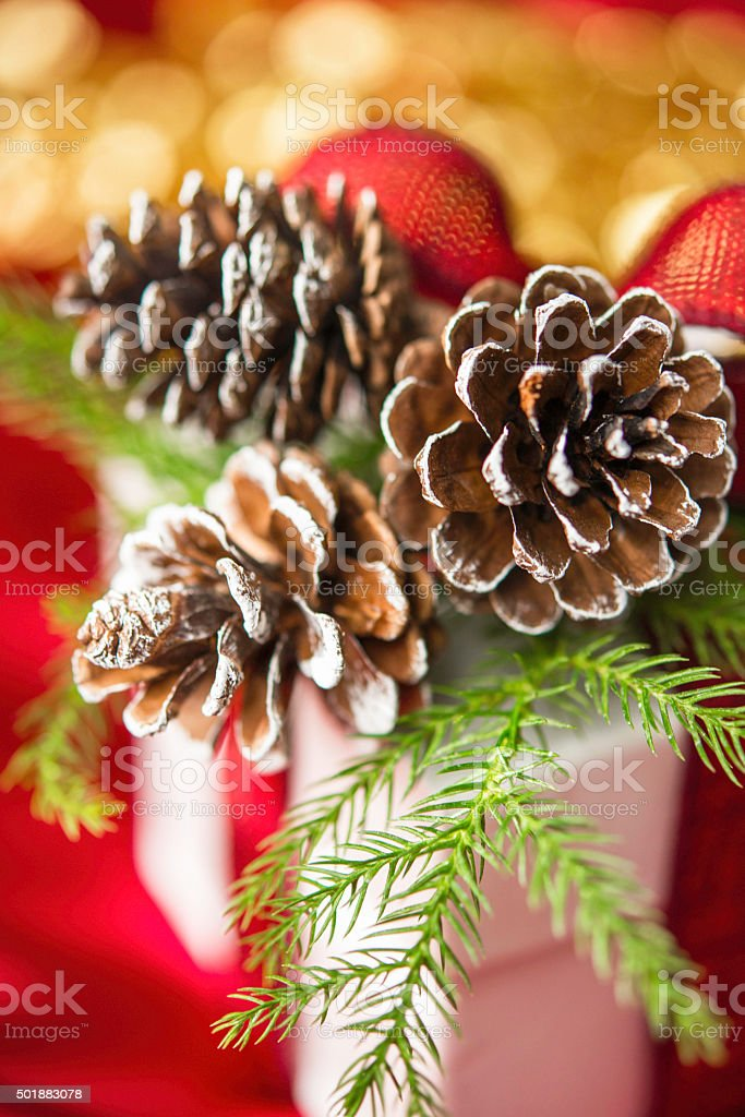 Christmas gift decorated with natural elements against red background stock photo
