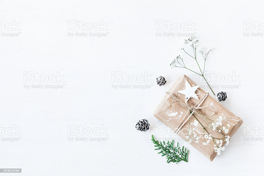 Christmas gift, pine cones, thuja branches, gypsophila flowers.Flat lay stock photo