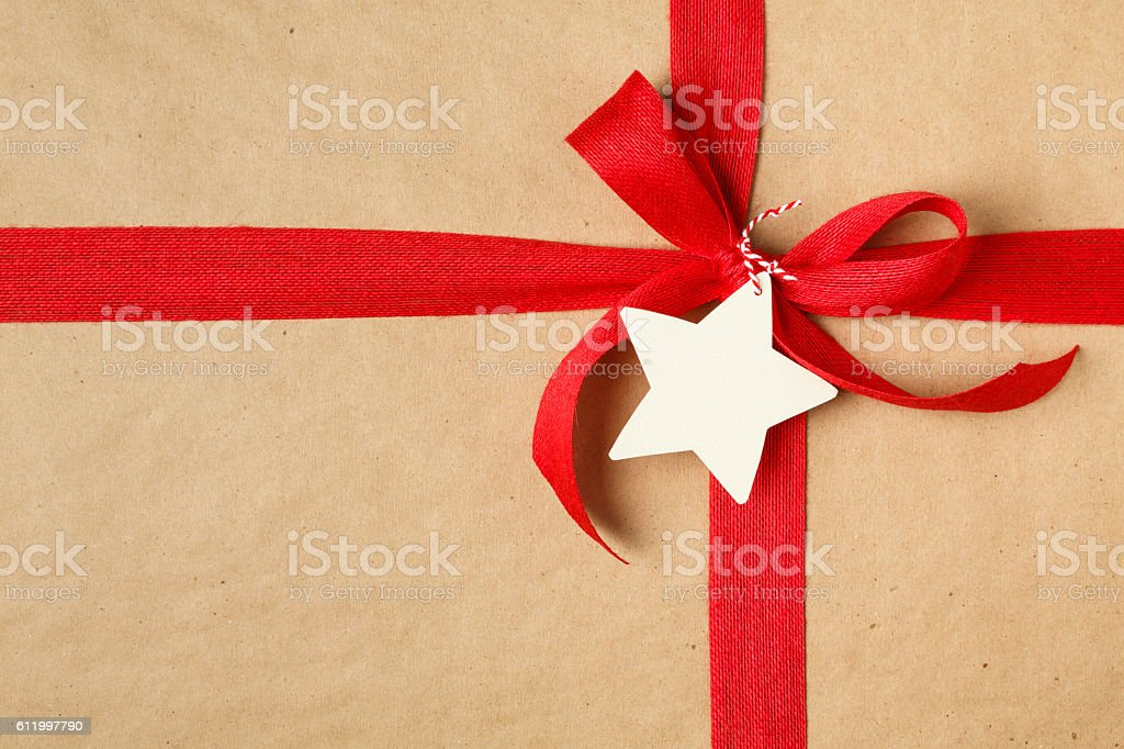 Christmas gift recycled wrapping paper gift tag red bow background stock photo