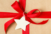 Christmas gift recycled wrapping paper gift tag red bow closeup