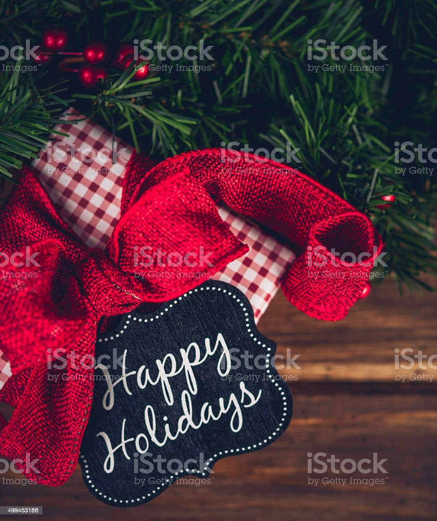 Christmas gift with evergreen garland and Happy Holidays message stock photo