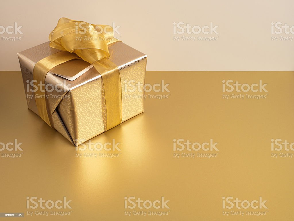 Christmas gift with gold ribbon and gold wrapping stock photo
