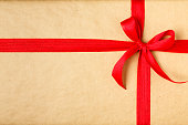 Christmas gift with recycled wrapping paper and red bow background