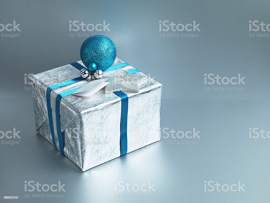 Christmas gift with silver wrapping and blue ribbon royalty-free stock photo