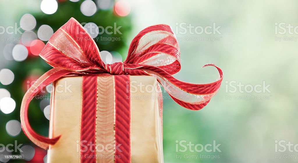 A Christmas gift wrapped in gold with a red bow royalty-free stock photo