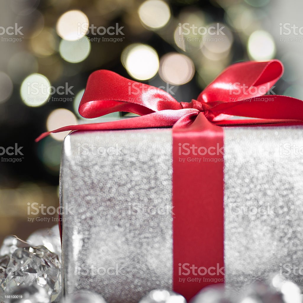 Christmas gift wrapped with red bow, close-up royalty-free stock photo