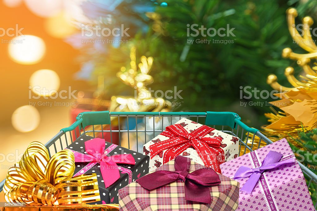 Christmas gifts and presents in shopping trolley with blurred lights stock photo