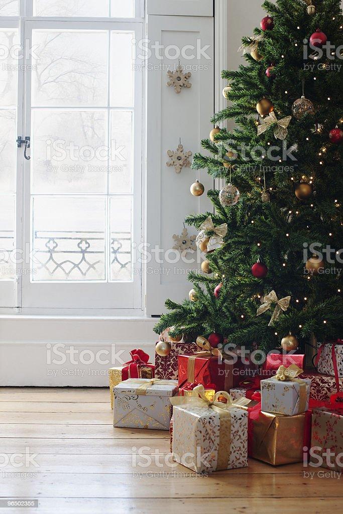Christmas gifts beneath tree near window royalty-free stock photo