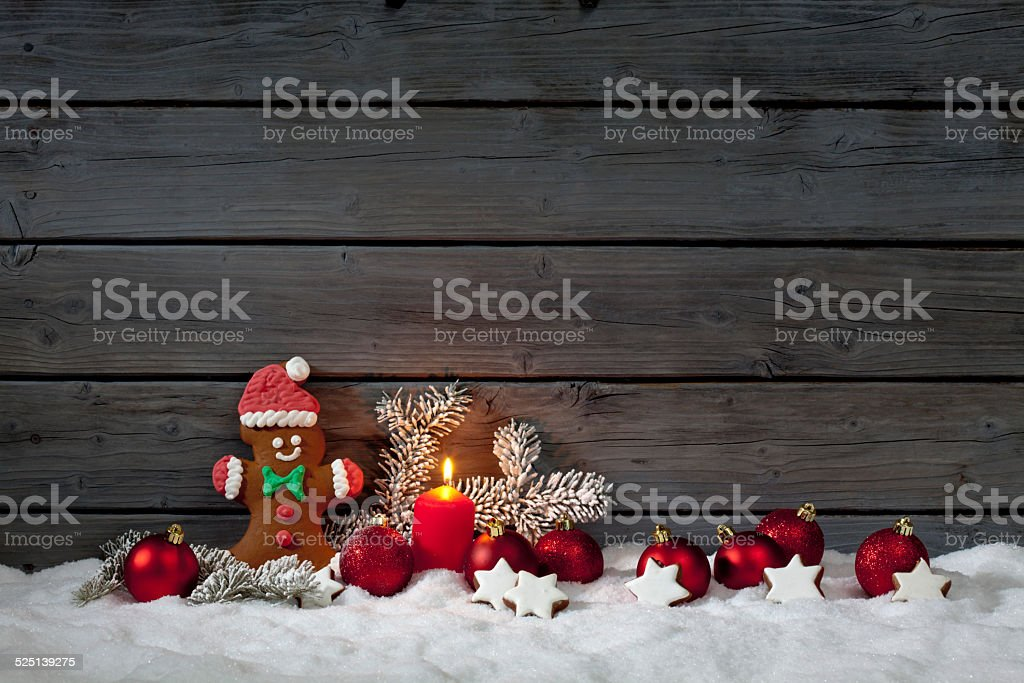 Christmas gingerbread bear on pile of snow against wooden wall stock photo