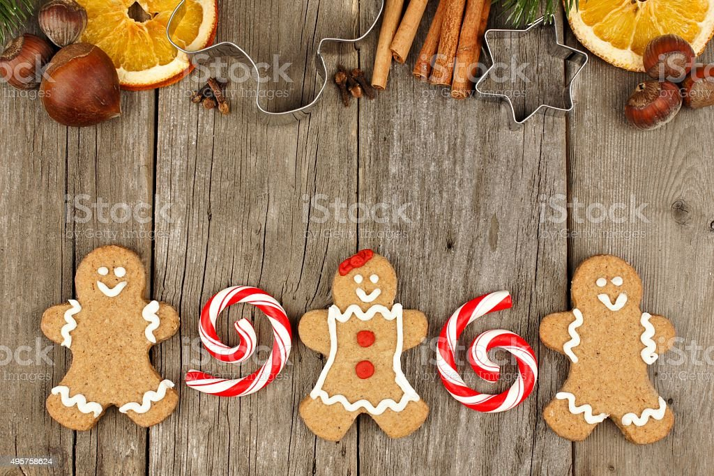 Christmas gingerbread cookies, peppermints and baking goods on rustic wood stock photo