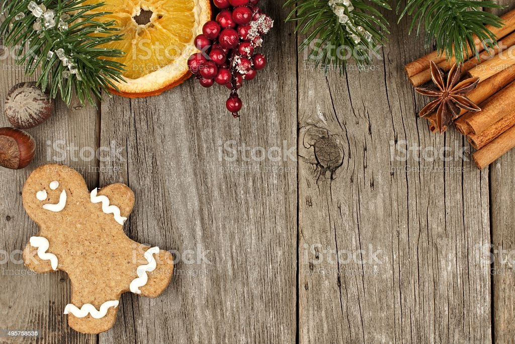 Christmas gingerbread man on wooden background with tree branch border stock photo
