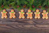Christmas gingerbread men cookies and fire tree on rustic wood