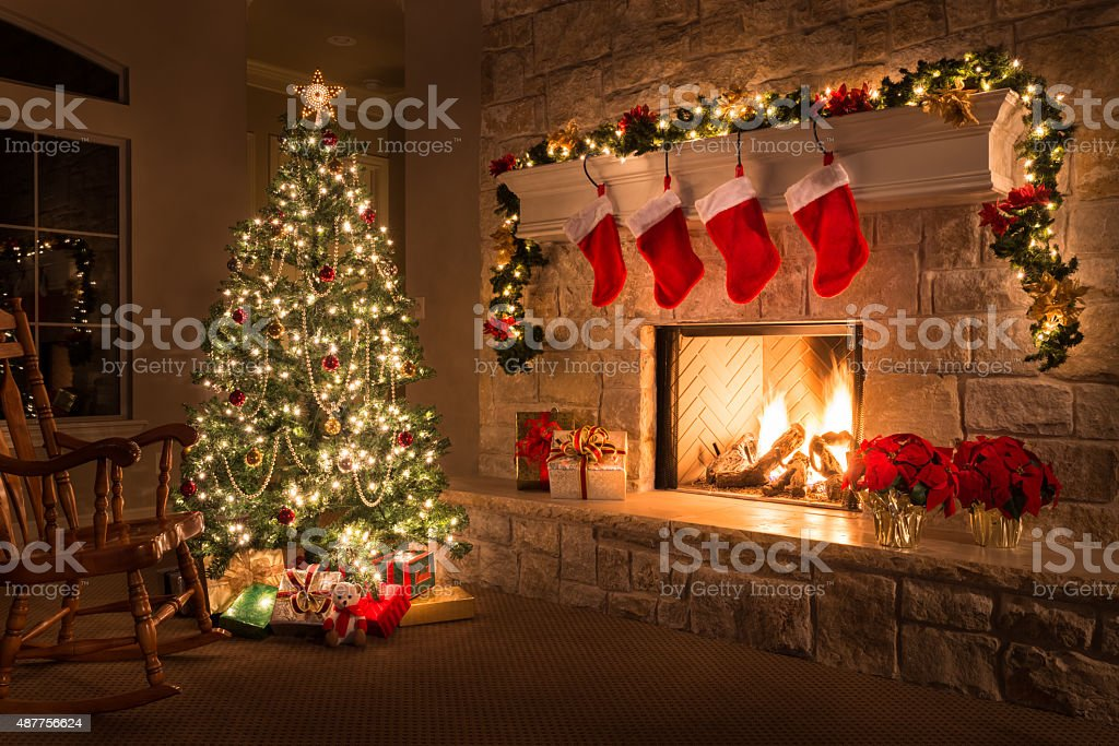 Christmas. Glowing fireplace, hearth, tree. Red stockings. Gifts and decorations. stock photo