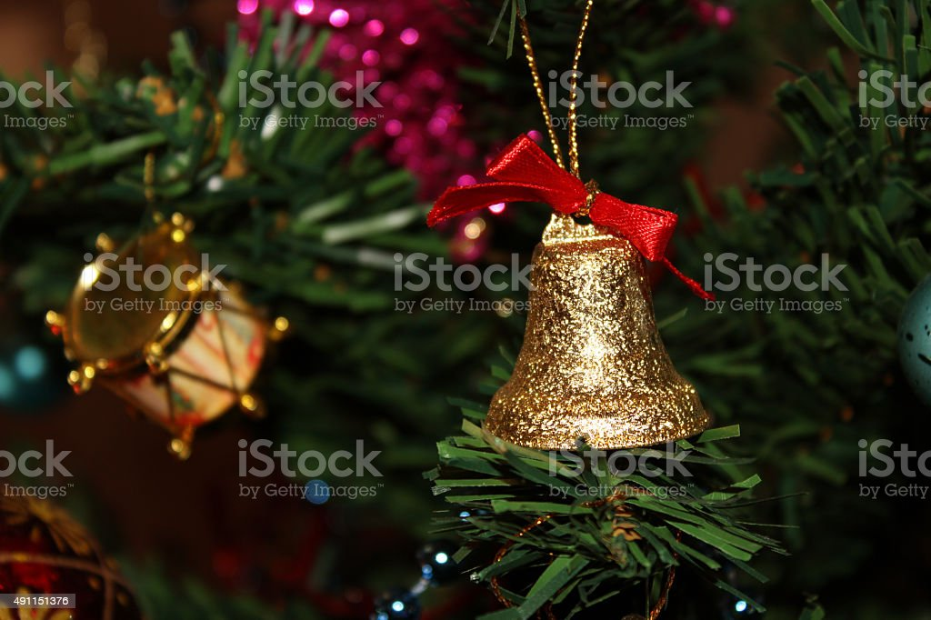 Christmas golden bell and drum on the tree stock photo