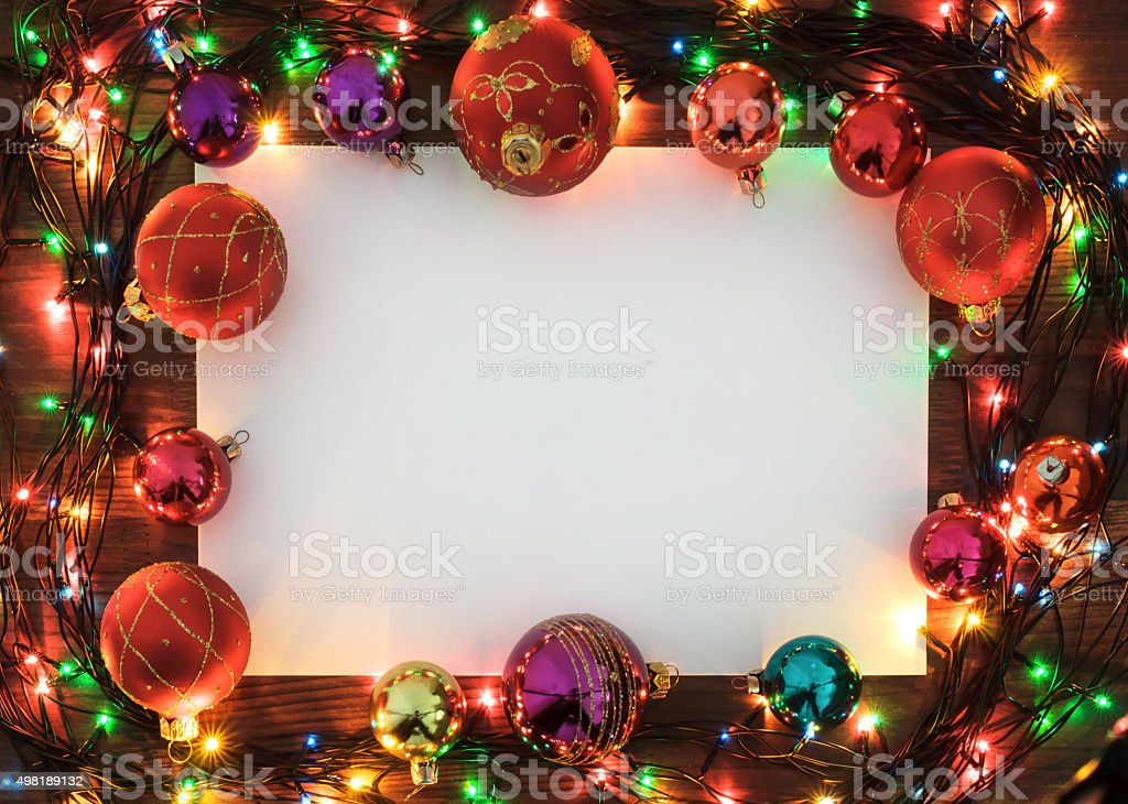 Christmas Greeting Card - Garland Frame on a wooden surface stock photo