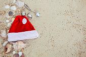 Christmas hat on the beach. Santa   the sand near shells