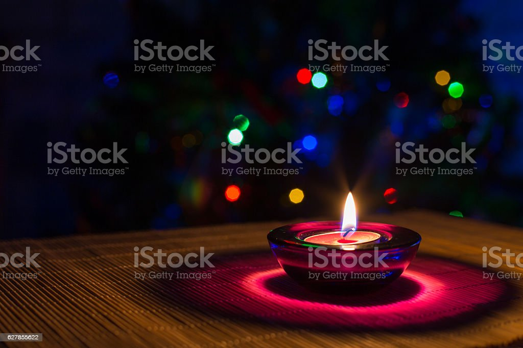 Christmas holiday background with purple candle and colorful lights stock photo