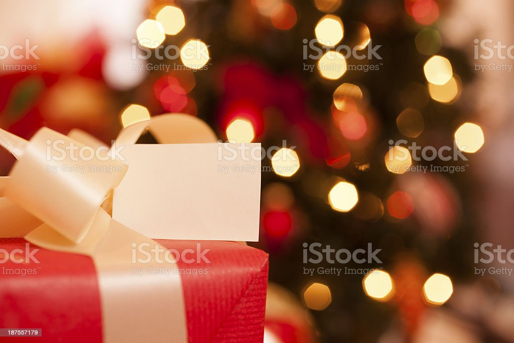 Christmas:  Holiday gift with blank tag. Lit tree in background. stock photo