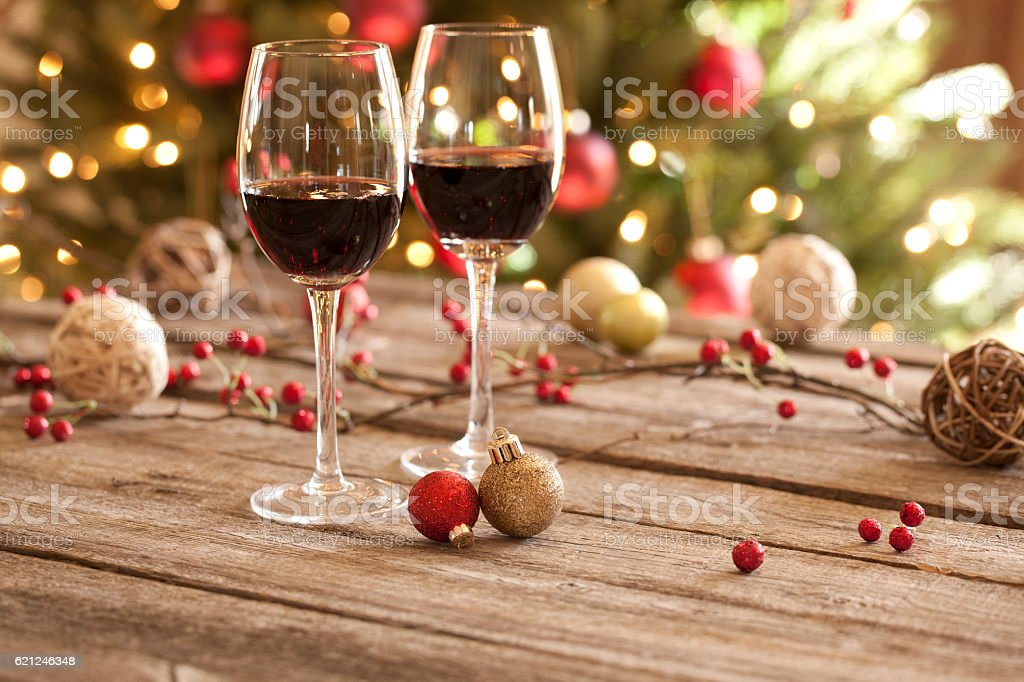 Christmas holiday red wine, old wood table, ornaments and tree stock photo