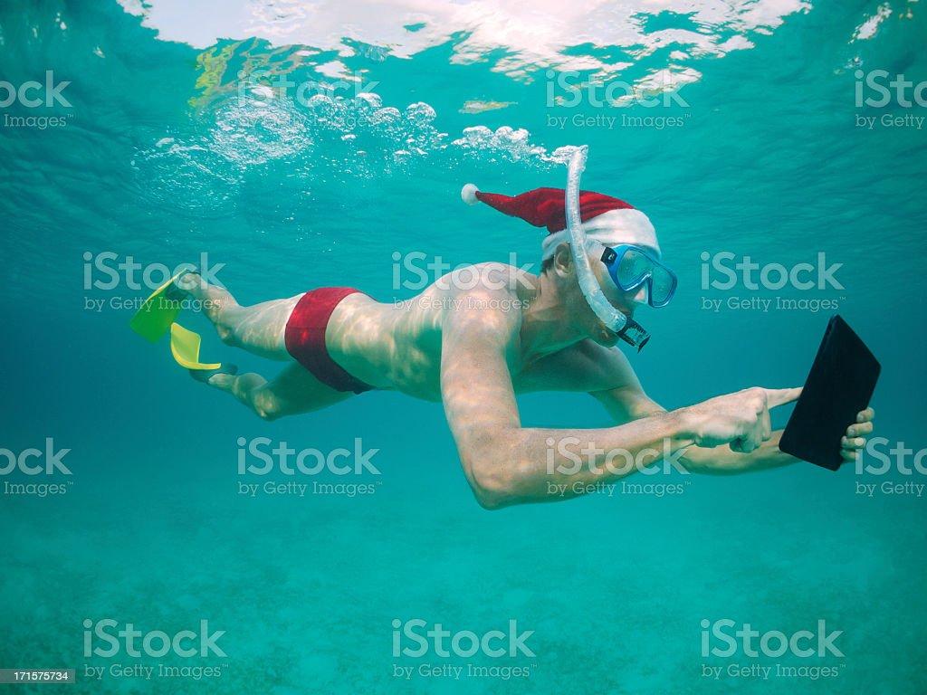 Christmas Holiday Traveling Santa Hat Man Snorkeling Using Digital Tablet royalty-free stock photo